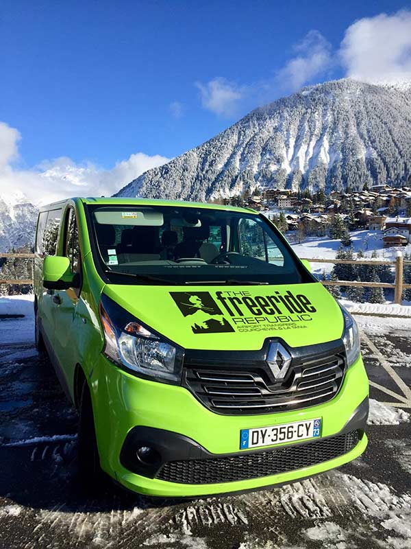 Green Freeride Republic Mini Bus with mountains in background.